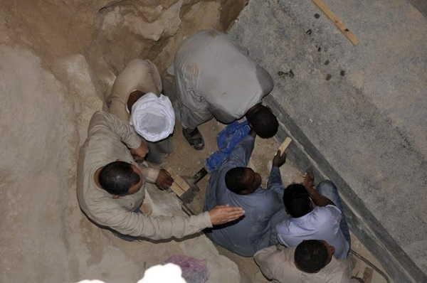 Esperti che aprono il sarcofago di granito.